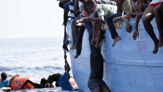 Illegal African migrant try help another man to climb inside boat for Mediterranean sea