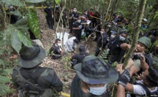 Policemen and reporters monitor as forensic experts dig out human remains near the abandoned human trafficking camp in the jungle close the Thailand border at Bukit Wang Burma in northern Malaysia in this 26 May 2015 file photo