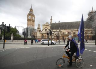 A protester wears a Boris Johnson face mask as he rides a tricycle.