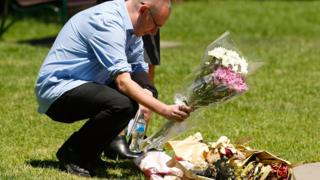 A man places flowers near a plaque honouring the victims of the incident