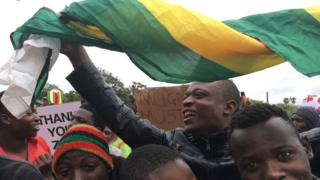 crowd with flag, sign reading Mugabe must go, people smiling