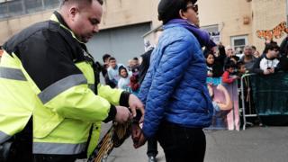 Agente del Servicio de Inmigración y Control de Aduanas arresta a una mujer.