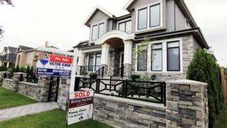 Realtors signs displayed outside a newly sold property in a Vancouver, British Columbia in Canada.