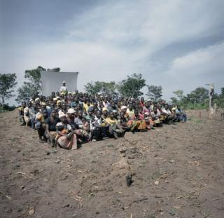 A group sit in a field.