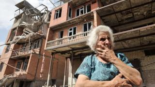 a Georgian woman in front of her home, which has been destroyed