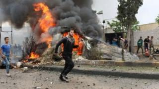 คนหลายคนพากันวิ่งหนี เบื้องหลังเป็นกองเพลิงไฟลุกโชน