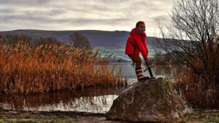 A photo of a child holding the Excalibur sword in the stone by the lake.