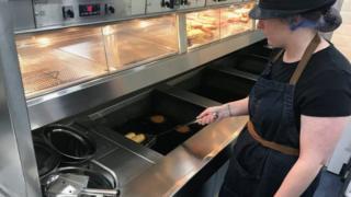 Staff member cooks at fryer