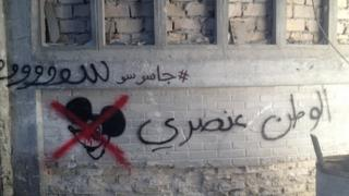 "Graffiti reading ""Homeland is racist"" on the set"