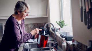 woman fills kettle