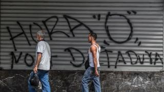 People in Venezuela walk past a graffiti that reads in Spanish