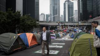 Occupy Central co-founder Benny Tai Yiu-ting (L) walks past tents at a pro-democracy protest site set up on a highway in the Admiralty district of Hong Kong on 4 November 2014