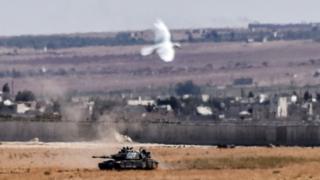 9月4日、トルコ南部キリス県エルベイリから撮影したシリア国境向こうのトルコ軍戦車と、その近くを飛ぶ鳥