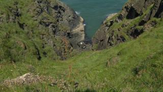 The car at the base of the cliff