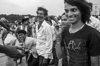Men laughing while celebrating Ganesh Chaturthi, a Hindu festival