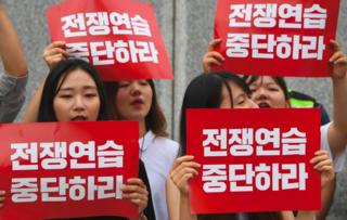 """South Korean protestors hold placards that read """"stop war exercise"""" during a rally denouncing the annual Ulchi Freedom Guardian (UFG) joint South Korea-US military exercise, near the US embassy in Seoul on 21 August 2017"""