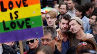 "Two men embrace behind a sign saying ""love is love"" at a rally for marriage equality in Australia"