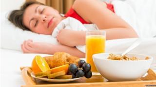 Mujer durmiendo frente a una bandeja de desayuno