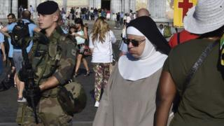 an armed soldier in full camouflage walking past a woman in a nun's habit, 15 August 2016