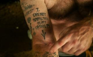 """Un tatuaje que dice: """"No puedo culpar a mi padre de esto"""", y señala una cicatriz de aguja vieja."""