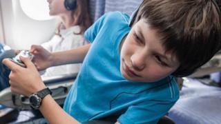 Un niño sentado en un asiento de avión, asomándose al pasillo
