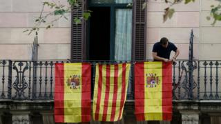 Spanish and Catalan flags from a balcony in Barcelona on October 10, 2017