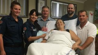 Billiana with her parents and the paramedics who delivered her