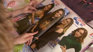 Girls look at pictures of Little Mix