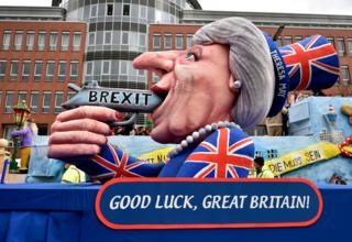 "A carnival float depicts British Prime Minister Theresa May with a gun and the writing ""Brexit"" on it prior to the traditional carnival parade in Duesseldorf, Germany, on Monday, Feb. 27, 2017."