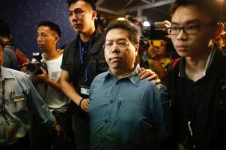 "This handout photo from The Initium taken and released on 15 August 2017 shows Democratic Party member Howard Lam (C, blue shirt) after his arrest for ""misleading police"" in Hong Kong."