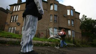 Children playing in front of a boarded up tenement in Glasgow