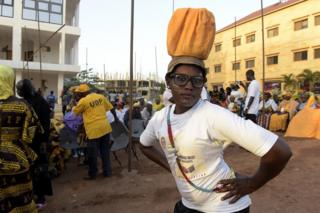 A supporter of a parliamentary candidate in The Gambia strikes a pose on Tuesday, two days before the first post-Jammeh polls