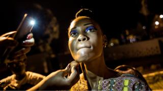 A Congolese fashion model is seen whilst she prepares her makeup backstage ahead of the Kinshasa Fashion Week on October 14, 2017 in Kinshasa.