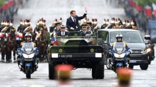 "New French president Emmanuel Macron (C) waves from a military vehicle driving on the city""s famous Champs Elysee boulevard as he arrives for a wreath laying ceremony at the Arc de Triomphe""s Unknown Soldier monument, following his official inauguration, in Paris, France, 14 May 2017"