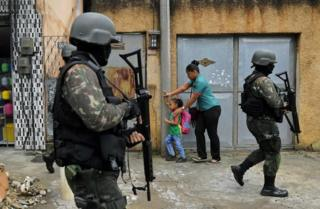 A mother and child walk past military police on patrol near the Vila Kennedy favela in Rio de Janeiro on February 23, 2018