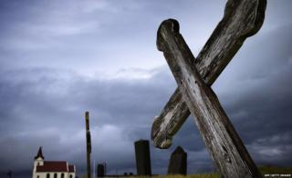 This picture taken on July 10, 2014 shows a cross in the cemetery and the church of Kjalvegur, southwest Iceland.