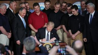 Trump with miners signing the order