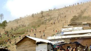 A file picture taken on May 28, 2013 shows people carrying bags of cassiterite (tin ore), coltan, which is used in mobile telephones and computers, and manganese down a hill from the Mudere mine, near Rubaya
