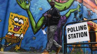 A young man walks past a polling station
