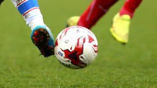 players feet kicking ball