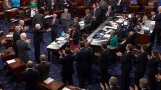 US Senator John McCain (R-AZ), who had been recuperating in Arizona after being diagnosed with brain cancer, acknowledging applause as he arrives on the floor of the U.S. Senate after returning to Washington for a vote on healthcare reform in Washington, US 25 July 2017