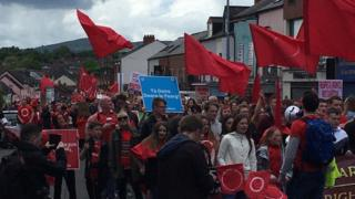 People are marching along the Falls Road into Belfast city centre