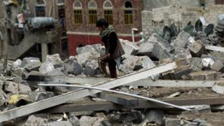 A Yemeni child inspects the rubble of a house