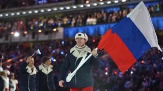 File photo taken in February 2014 shows Russia's flag bearer, bobsledder Alexander Zubkov, leading his national delegation during the Opening Ceremony of the Sochi Winter Olympics
