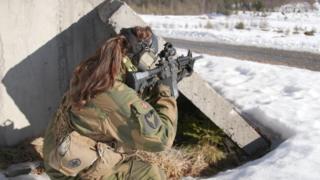 Женщина-солдат стреляет из пистолета-пулемета