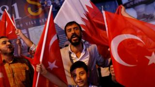 People shout slogans as they hold Turkish and Qatari flags during a demonstration in favour of Qatar in Istanbul, Turkey (7 June 2017)