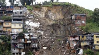 Rescue workers survey an area where a landslide destroyed several homes in Manizales, Caldas, Colombia