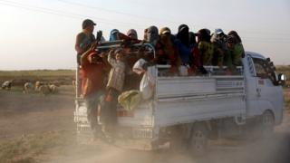 Residents displaced by fighting between Syrian Democratic Forces and Islamic State militants ride on a truck near Raqqa