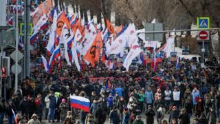 Moskvada müxtəlif plakat və bayraqlar daşıyan yürüş iştirakçıları