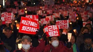 """Жители Южной Кореи вышли на улицы, требуя отставки президента, с плакатами """"Пак Кын Хе, уходи""""."""
